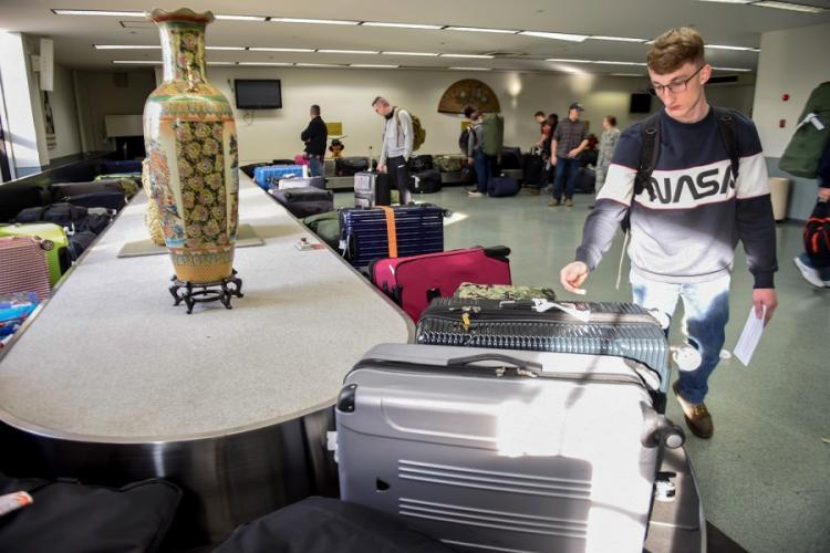 A Patriot Express flyer retrieves his luggage inside the passenger terminal at Yokota Air Base, Japan, Nov. 28, 2018. GABRIELLE SPALDING/U.S. AIR FORCE
