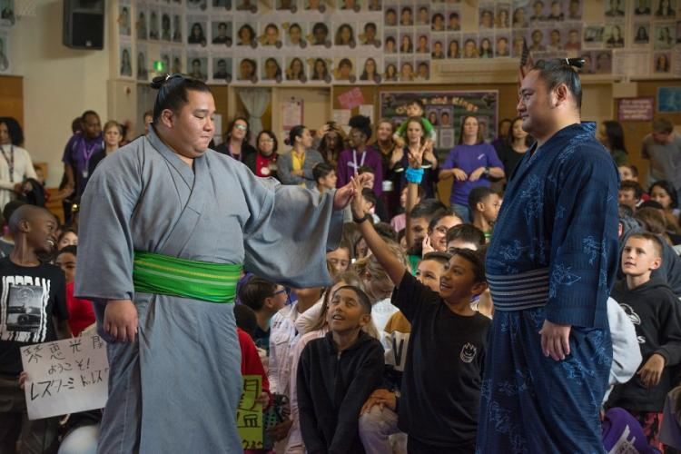 Sumo wrestler Kotoeko, right, watches as Kotooodutsu high-fives a Lester Middle School student at Camp Lester, Okinawa, Friday, Dec. 13, 2019. CARLOS VAZQUEZ/STARS AND STRIPES