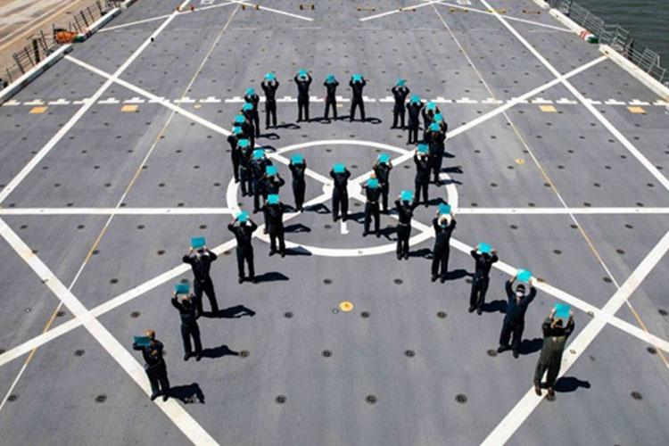 Sailors assigned to the San Antonio-class amphibious transport dock ship USS Arlington form a teal ribbon on the flight deck for Sexual Assault Awareness Month, April 26, 2021. The teal ribbon represents a symbol of support for the cause (Photo by: Navy Petty Officer 2ndClass John Bellino).