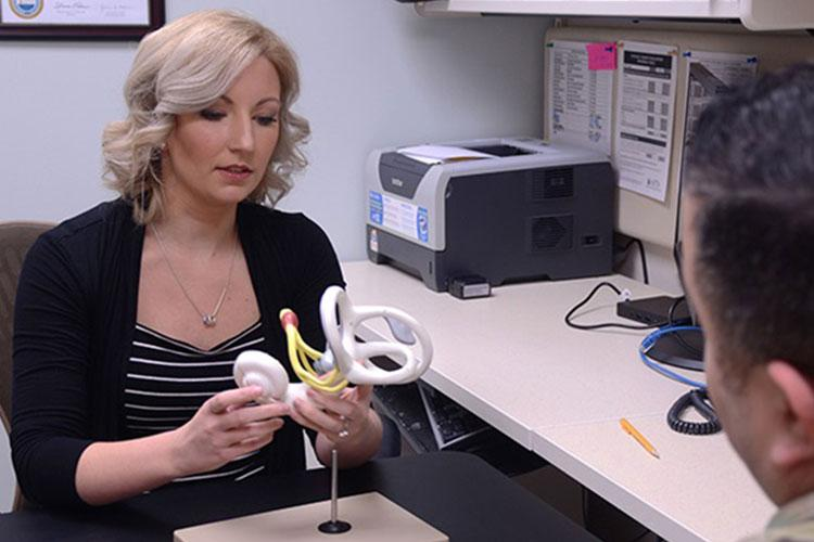Elizabeth Kirkpatrick, the physical therapist for the Fort Drum Traumatic Brain Injury Clinic at Fort Drum, New York, uses a model of the inner ear to show how a concussion can lead to dizziness and other problems. (Photo by Warren Wright Jr., Fort Drum MEDDAC.)