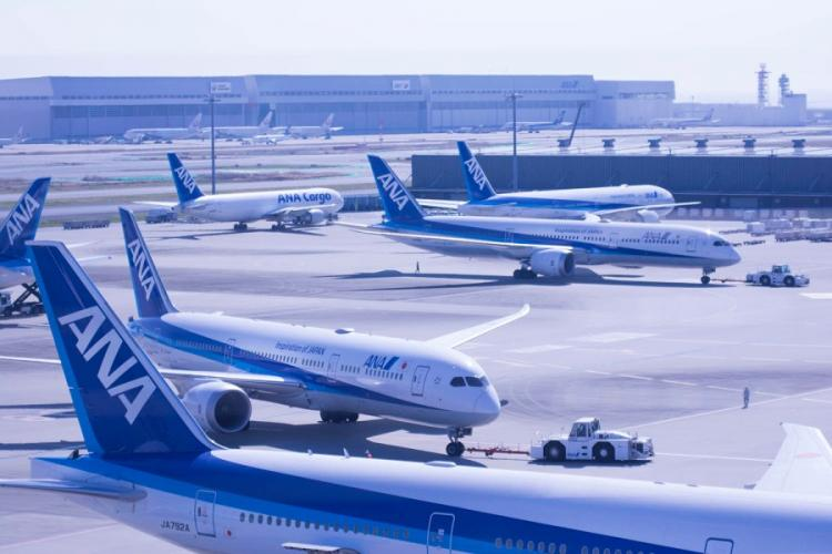 Commercial jets are pulled to their gates at Haneda International Airport in Tokyo, March 18, 2020. AKIFUMI ISHIKAWA/STARS AND STRIP