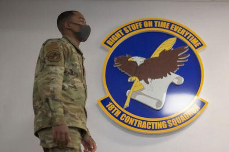 U.S. Air Force 2nd Lt. Jonathan Woods, 18th Contracting Squadron contract specialist, passes by the squadron emblem at Kadena Air Base, Japan, Sept. 2, 2021. The squadron acts as an executive agent responsible for supporting all military family housing across Okinawa. (U.S. Air Force photo by Senior Airman Demond Mcghee)
