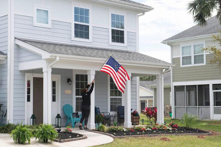 A resident at Balfour Beatty Housing raises the American flag at her home at an on-base military housing community at Naval Station Mayport, Fla., on March 18, 2019. (DEVIN BOWSER/U.S. NAVY)
