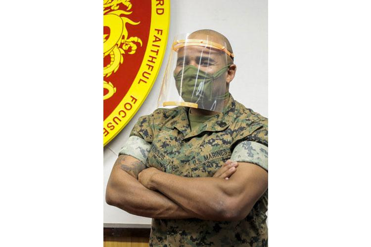 U.S. Marine, Staff Sgt. Quincy Reynolds, the innovation officer with 3d Maintenance Battalion, 3d Marine Logistics Group, displays a mask created from a 3D printer on Camp Courtney, April 15, 2020. Marines and sailors with III Marine Expeditionary Force are using cutting-edge additive manufacturing technology here to mass produce and distribute personal protective equipment in the fight against COVID-19. (U.S Marine Corps photo by Cpl. Nickolas C. Beamish)