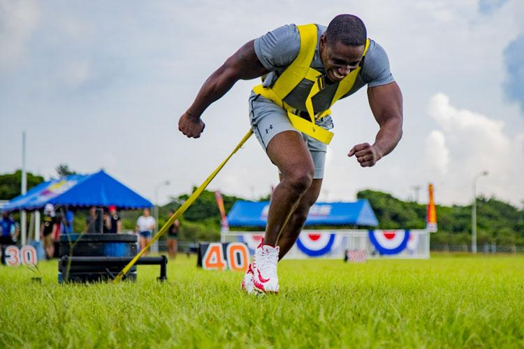 U.S. Marine Corps Staff Sgt. Reginald Berry the chief instructor for the Staff Noncommissioned Officers Academy, pulls a weighted sled in the sled pull event in Okinawa's Strongest Battle of the North, Aug. 18, 2019, Camp Hansen, Okinawa, Japan. The competition challenges men and women to compete in physically demanding events to find the strongest on the island. (U.S. Marine Corps photo by Lance Cpl. Karis Mattingly)