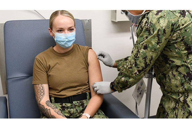A hospital corpsman prepares a sailor's arm before administering a vaccine at the Navy Medical Readiness and Training Command, Pearl Harbor, Hawaii, immunization clinic. (Photo by Macy Hinds)