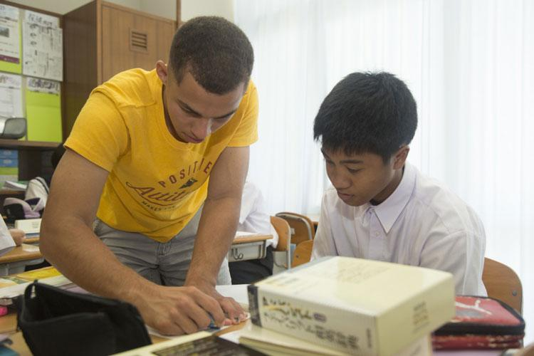 Lance Cpl. Luis A. Melendez Irizarry, a motor transport operator with Ie Shima Training, corrects student's grammar Sept. 13 in Ie Village, Okinawa. The weekly cultural exchange started in February was initiated with the purpose of finding ways for students to practice the English they learned in class. (Photo by Nika Nashiro)