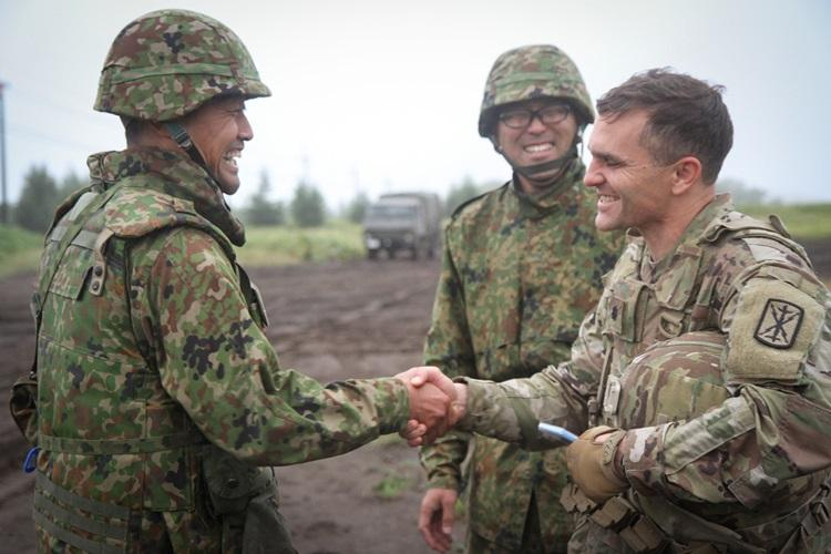 U.S. Army Lt. Col. Timothy Lynch, commander of 5th Battalion 3rd Field Artillery Regiment shakes hands with the battalion commander of Western Army Field Artillery of the Japan Ground Self-Defense Force at Yausubetsu Training Area, Japan, Sept. 16. (Photo Credit: Capt. Rachael Jeffcoat)