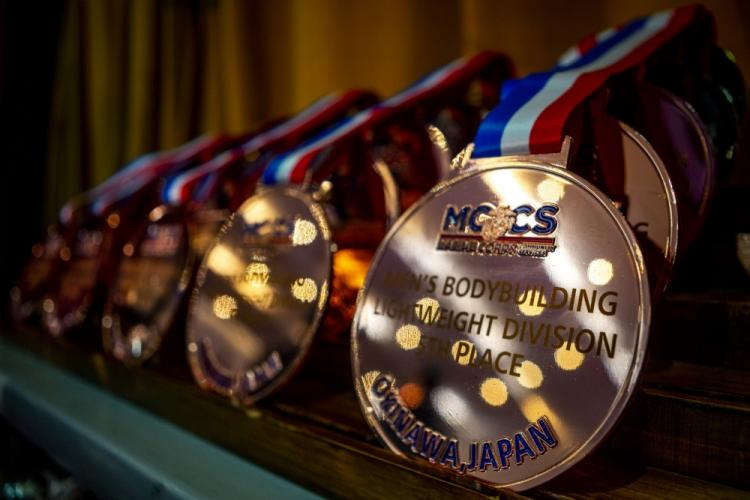 """Awards are displayed prior to the start of the Far East Bodybuilding Competition on Camp Foster, Okinawa, Japan, August 4, 2019. The competition allowed participants from all over the world to display their stage-worthy physiques and compete for the title of """"champion."""" (U.S. Marine Corps photo by Cpl. Christopher A. Madero)"""