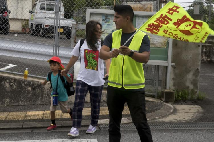 U.S. Marine Corps Pfc. Alfonso Padilla, guides a local elementary school child and his mother at a crosswalk July 18, 2019. Crossing guard duty is one of the multiple tasks conducted by Marine volunteers on Okinawa. (U.S. Marine Corps photo by Pfc. Colton K. Garrett)