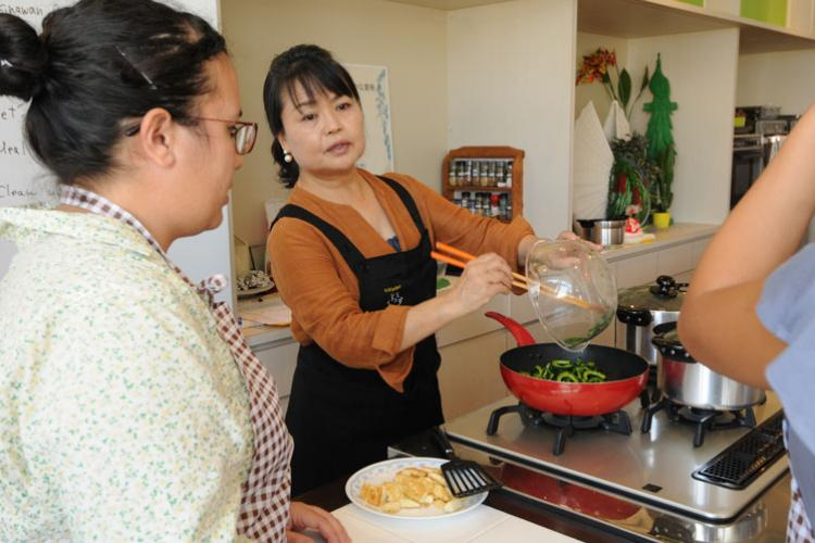 Instructor Kae Izena demonstrates proper cooking technique for the students. (Photos by Shoji Kudaka, Stripes Okinawa)