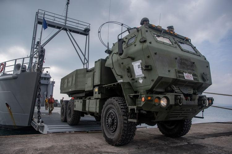 U.S. Marines with 12th Marine Regiment, 3rd Marine Division, and U.S. Soldiers with 97th Transportation Company, 10th Support Group, work together to quickly embark transportation vehicles and a High Mobility Artillery Rocket System on the U.S. Army Vessel Harpers Ferry (LCU-2022) during a joint service HIMARS embarkation training exercise in Kin, Okinawa, Japan, Oct. 31, 2019. (U.S. Marine Corps photo by Lance Cpl. D'Angelo Yanez)