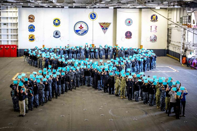 NORFOLK (April 18, 2018) Sailors aboard the aircraft carrier USS George H.W. Bush (CVN 77) stand in the shape of a ribbon holding teal paper to recognize Sexual Assault Awareness and Prevention Month (SAAPM). The ribbon represents the crew's commitment to removing toxic behaviors like sexual assault from the ranks of the military. (U.S. Navy photo by Mass Communication Specialist 2nd Class Hank Gettys)