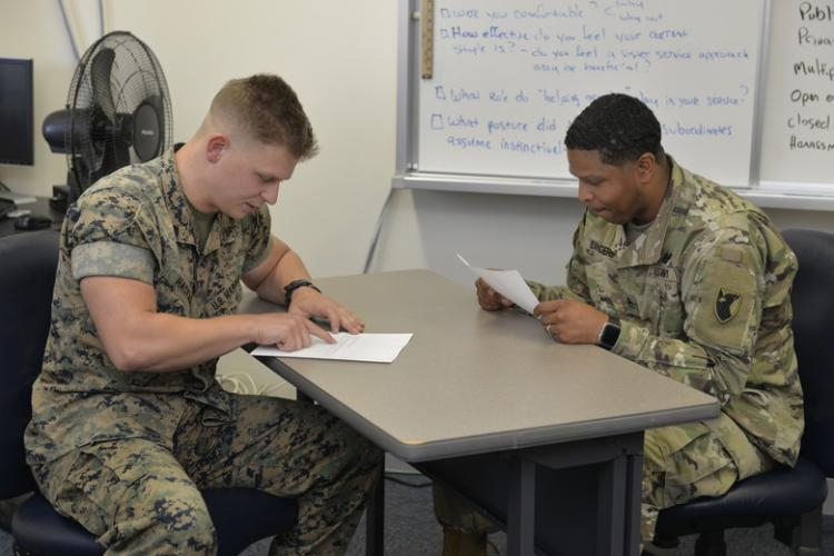 Two service members discuss best counseling procedures during the Okinawa Joint PME Experience April 1, 2019, at Kadena Air Base, Japan. With the military becoming more and more integrated in order to ensure mission success, leaders at every level must know and be comfortable operating in a joint environment. (U.S. Air Force photo by Staff Sgt. Benjamin Sutton)
