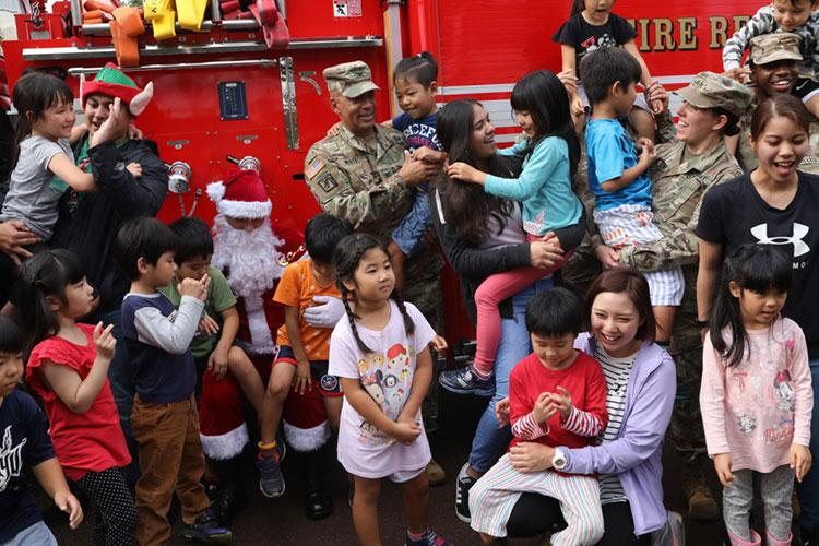 YOMITAN, OKINAWA, JAPAN – Col. Theodore White (center, holding a child), commander of the 10th Support Group, took an active part in maintaining important ties with the local community. Of course that task becomes much more pleasant when you bring Santa to children on a fire truck!