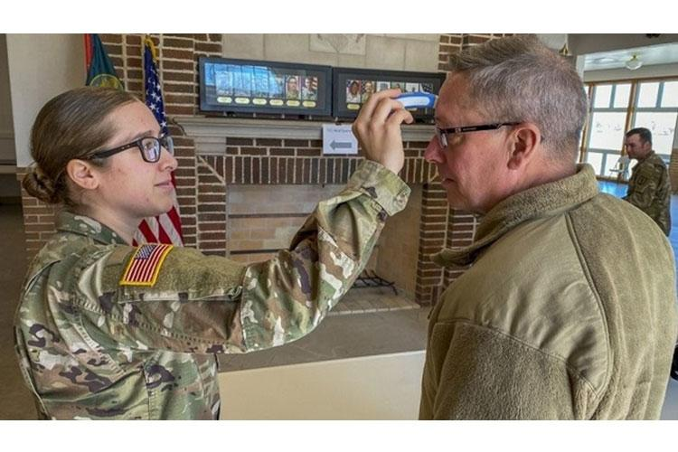 Sgt. Kate Cole, a medic with the 209th Regiment (Regional Training Institute) does a temperature check for Maj. Gen. Daryl Bohac, Nebraska adjutant general, as he enters Memorial Hall for an officer candidate commissioning ceremony March 20, 2020, at the Camp Ashland Training Site, Nebraska. (Nebraska National Guard photo by Sgt. Lisa Crawford)