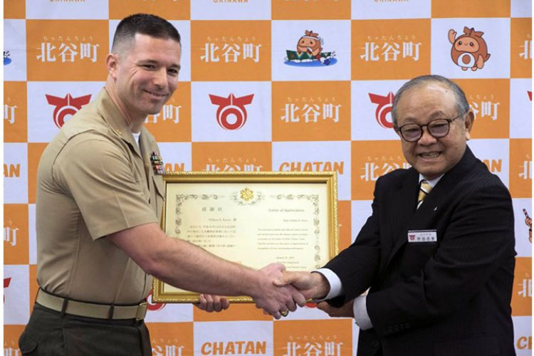 Marine Maj. William Easter, left, of the III Marine Expeditionary Force on Okinawa, receives a letter of appreciation Tuesday, Jan. 22, 2019, from Chatan Mayor Masaharu Noguni for a rescue at sea in December.  MATT BURKE/STARS AND STRIPES
