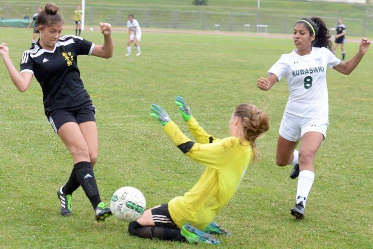 Kadena's Alexa Smith and Kubasaki goalkeeper Abbigail Irwin nearly collide after Smith sends a shot wide of the net, as Dragons' Angelica Figueroa looks on during Friday's Okinawa girls soccer match. The Panthers won 7-2 to sweep the season series. DAVE ORNAUER/STARS AND STRIPES