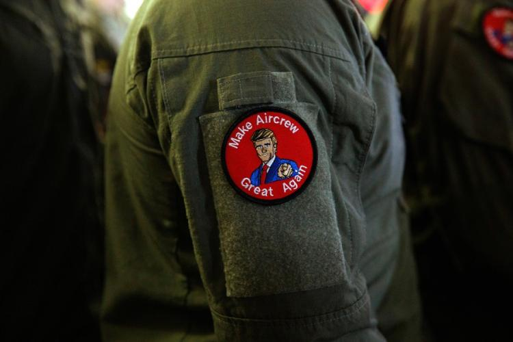 """A servicemember wears a patch that says """"Make Aircrew Great Again"""" while listening to President Donald Trump speak at a Memorial Day event aboard the USS Wasp on Tuesday, May 28, 2019, in Yokosuka, Japan. The patch includes a likeness of Trump. EVAN VUCCI/AP"""
