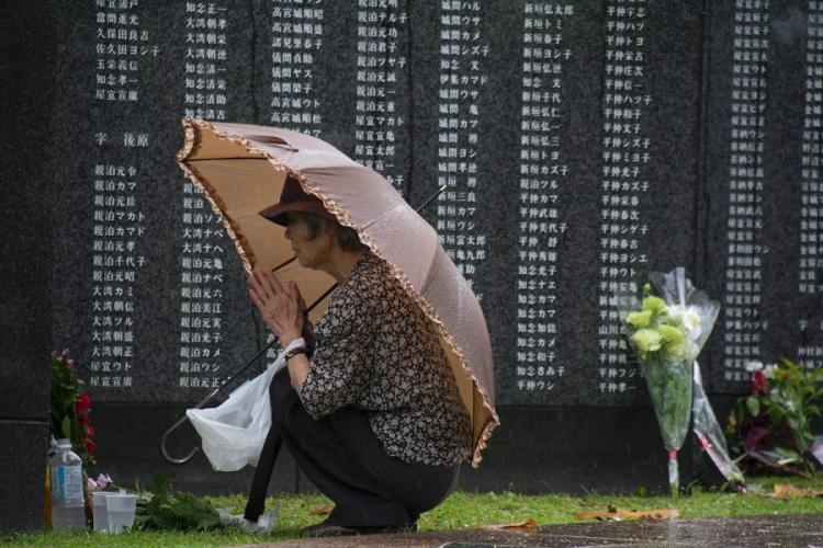 A visitor prays in front of the Cornerstone of Peace monuments at Okinawa Peace Memorial Park during the Irei no Hi ceremony, Sunday, June 23, 2019. CARLOS VAZQUEZ/STARS AND STRIPES