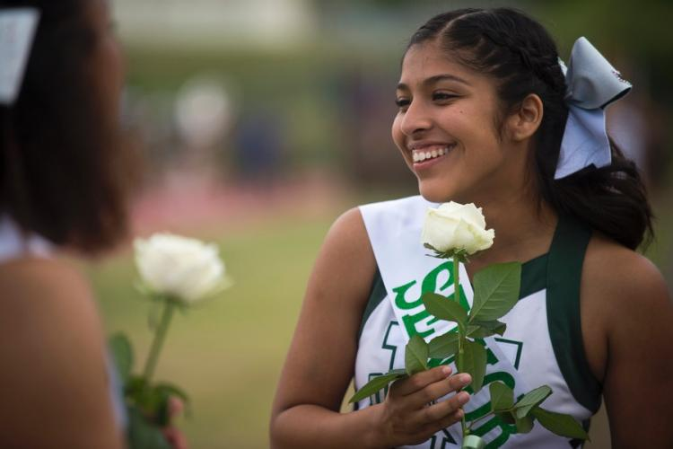 A senior cheerleader from Kubasaki High School speaks with her classmates ahead of the Dragons' homecoming matchup with the Camp Humphreys Blackhawks at Camp Foster, Okinawa, Friday, Oct. 25, 2019. CARLOS M. VAZQUEZ II/STARS AND STRIPES