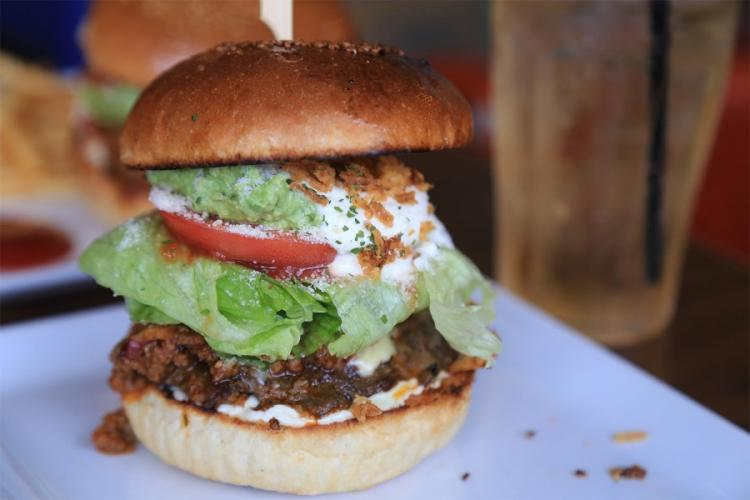 The Mexican Taco Burger from Captain Kangaroo on Okinawa features a chunky beef patty, melted cheese, guacamole, tomato, sour cream and chili beans. AYA ICHIHASHI/STARS AND STRIPES