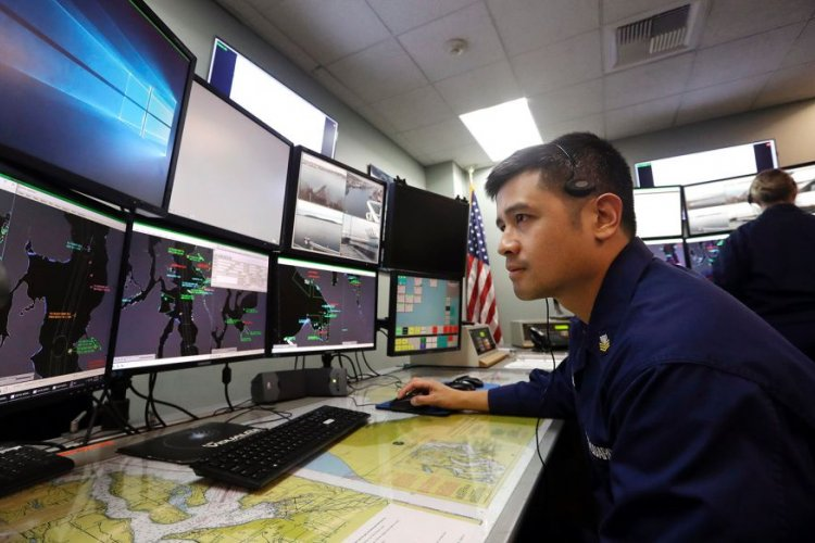 In a Wednesday, Jan. 16, 2019 file photo, U.S. Coast Guardsmen Gustavo Rosas, who missed his first paycheck a day earlier during the partial government shutdown, monitors marine vessel traffic at Sector Puget Sound base in Seattle.  ELAINE THOMPSON/AP