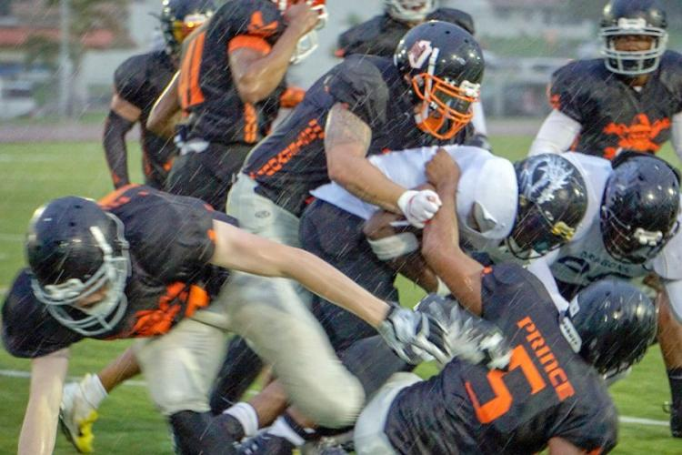 Hansen's Caine Collins leads a pack of Hansen Outlaws defenders, bringing down an Okinawa Dragons ballcarrier in the driving rain of the second quarter of the Torii Bowl. RADHIKA HANZLEY/SPECIAL TO STRIPES