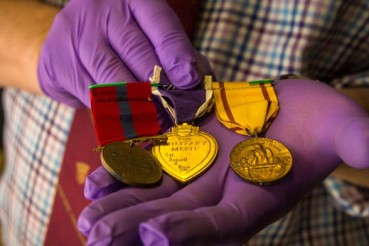 Owen Conner, uniforms and heraldry curator with the National Museum of the Marine Corps, inspects medal collection belonging to U.S. Marine Corps Sgt. Russell Rose at warehouse 2288, Marine Corps Base Camp Pendleton, California, Jan. 10, 2019. (Cpl. Juan Bustos/U.S. Marine Corps photo)