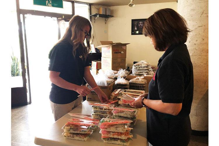 Help Oki volunteers Aubrie Owens, left, and Yoko Nesbitt prepare bento lunch boxes for needy Okinawans, Thursday, March 12, 2020. AYA ICHIHASHI/STARS AND STRIPES