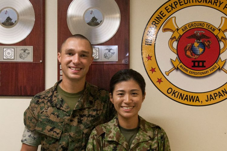 Corey and Shiori Danni pose for a photo in the III Marine Expeditionary Force Band hall on Camp Foster, Okinawa, Japan, Aug. 31, 2018. U.S. Marine Sgt. Corey Danni, a euphonium player with III Marine Expeditionary Force Band, and Japan Ground Self-Defense Force Leading Private Shiori Danni, a French horn player with the 15th Brigade Band, married in May 2018. (Photo by Nika Nashiro/Marine Corps Installations Pacific)