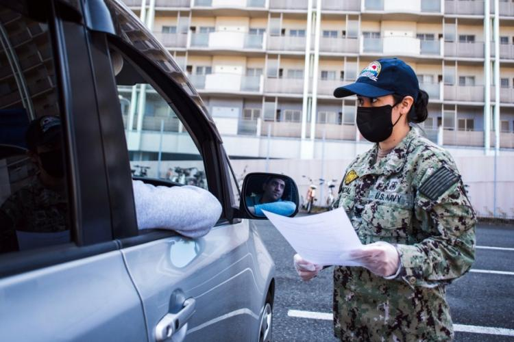 A sailor practices screening drivers for coronavirus symptoms at Yokosuka Naval Base, Japan, March 18, 2020. TAYLOR CURRY/U.S. NAVY
