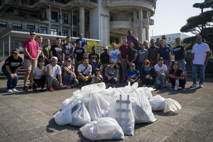 Members of the U.S. and local communities pose for a group photo after the monthly Friendship Cleanup in Uruma City, Okinawa, Japan on Oct. 5, 2019. The Single Marine Program coordinates the cleanup every month to provide service members the opportunity to volunteer for community service and build friendly relationships with the local community. (U.S. Marine Corps photo by Lance Cpl. Kindo Go)