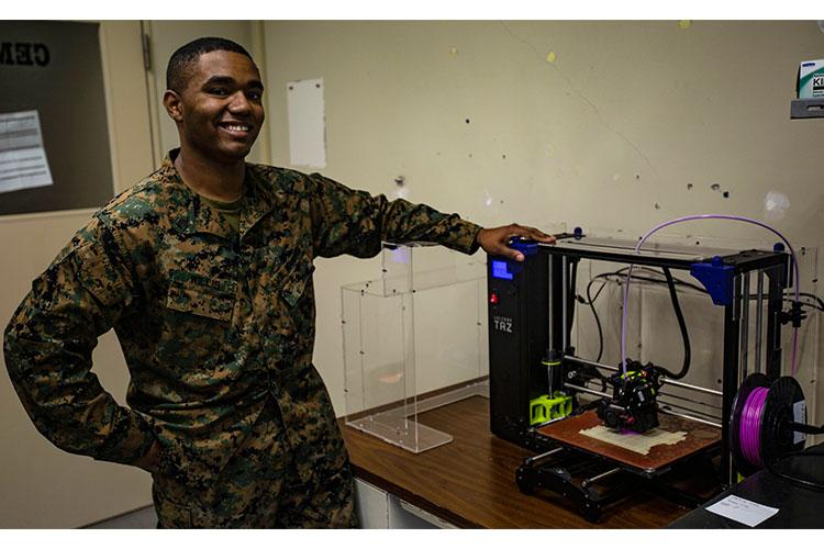 U.S. Marine Corps Sgt. Adrian J. Willis, a computer technician with 7th Communications Battalion, pictured here aboard Marine Corps Base Camp Hansen in Okinawa, Japan, is one of the Marines that utilize 3D printing technology to expand capabilities within the unit. Willis, from Las Vegas, Nev., is in charge of expanding the printer's capabilities and establishing the standard operating procedures for the printer in order to implement and track its impact in the unit. (U.S. Marine Corps Cpl. George Melendez)